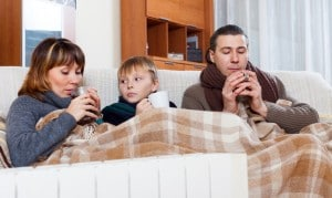 freezing family of three warming near warm radiator
