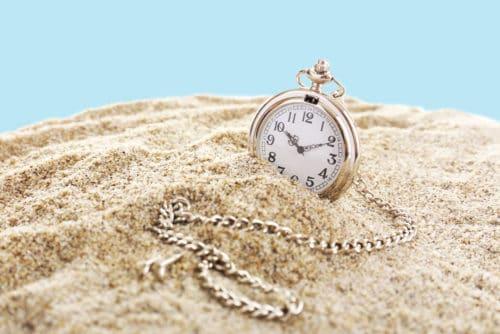 Silver pocket clock on sand